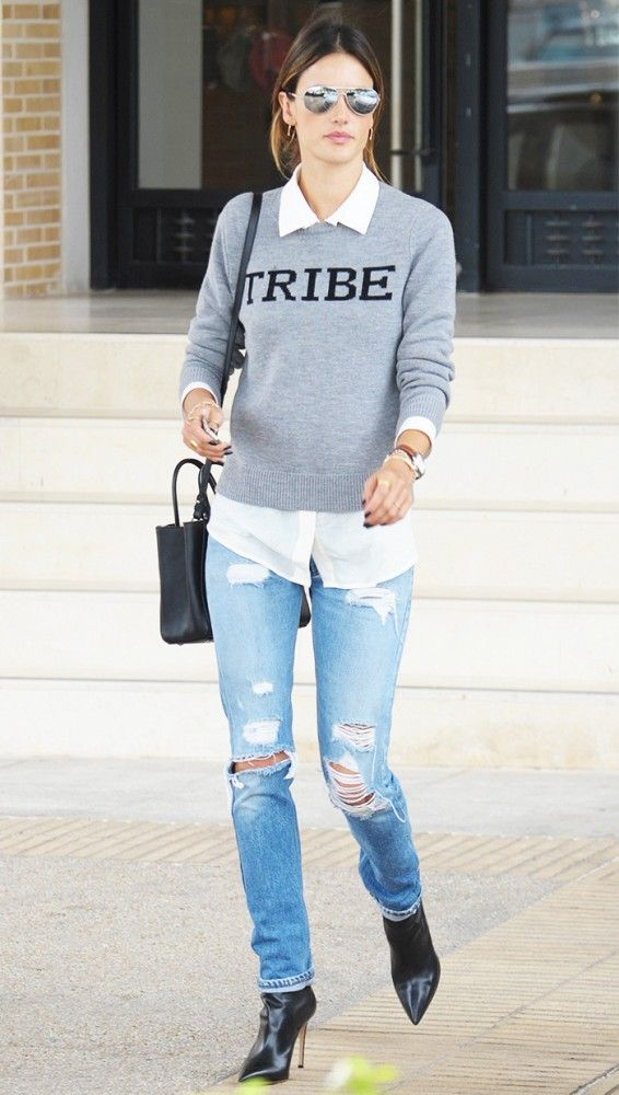 "Alessandra Ambrosio in a gray ""Tribe"" sweater, white button-down, distressed jeans, black booties, and a black satchel bag"