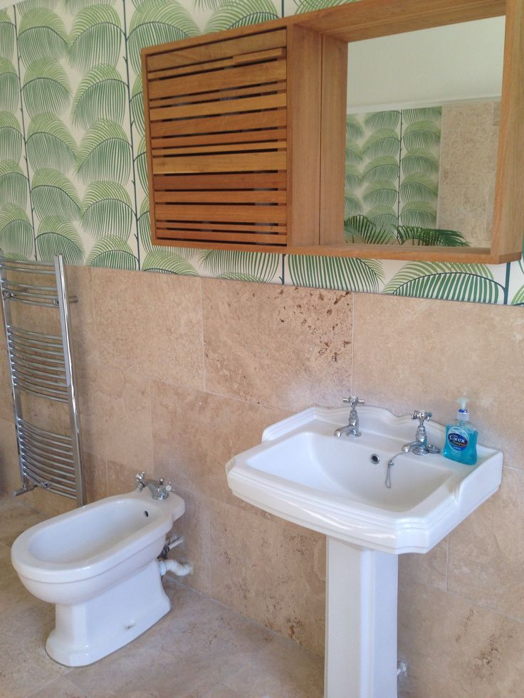 Sink in palm guest bathroom - wood accessories and Venetian blinds create clean yet tropical feel