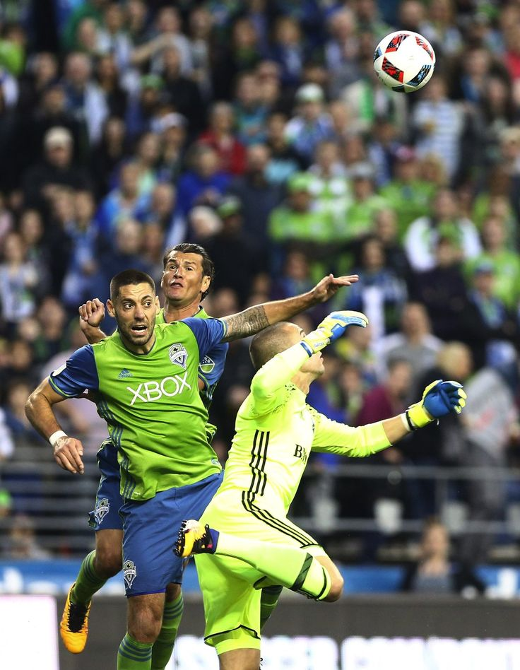 Montreal Impact goalkeeper Evan Bush clears the ball from the box as Sounders FC forward Clint Dempsey, left, and forward Nelson Valdez try to head it in during the first half of Saturday's game at CenturyLink Field in Seattle. The Sounders net their first win of season with a 1-0 victory over Montreal. (Lindsey Wasson / The Seattle Times)