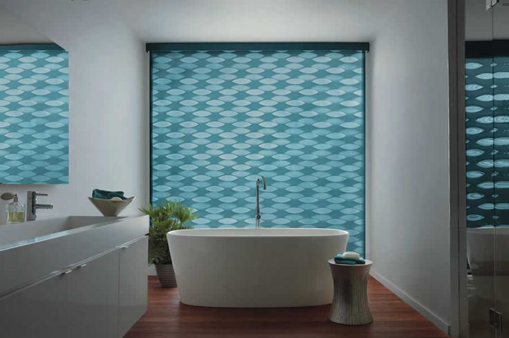 """Challenge: A client wanted to ensure complete privacy in the bathroom of her new home.  The counter and cabinetry in the bathroom were simple and modern, so she also wanted to """"spice up"""" the design.    Solution:  We chose a Designer Banded Shade.  She was able to keep the bands within the shade staggered to ensure privacy while letting some light in the room. The design of the shade also provided quite a statement."""