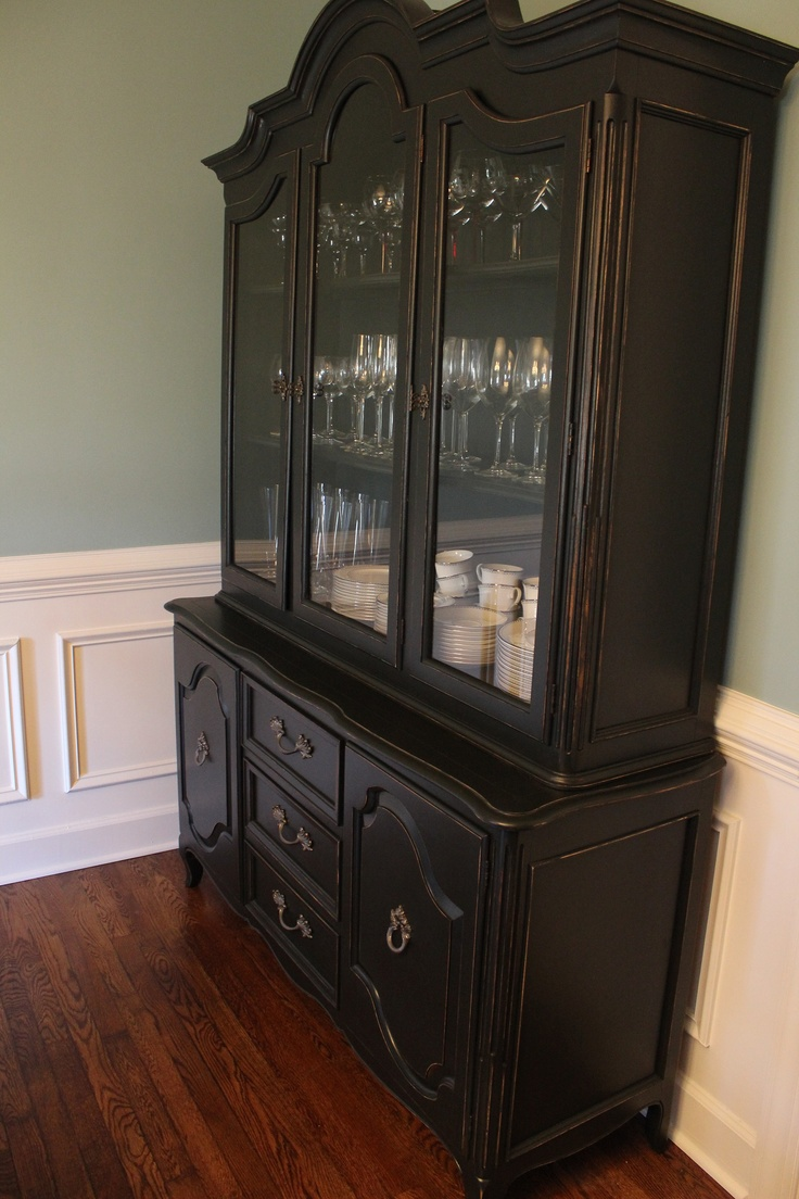 Vintage china cabinet painted in black latex and distressed. The black paint adds a modern edge to a traditional piece.