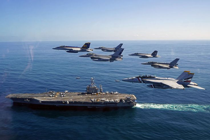 Cool photo of fighter jets flying over an aircraft carrier