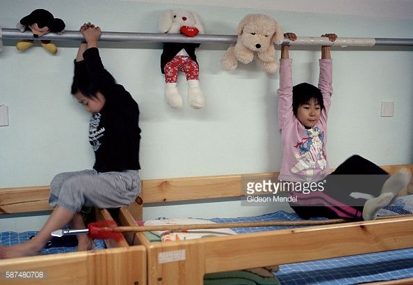 Young gymnast Zhao Chaoyue (8) plays with a friend on her bunk in their dormitory at the Shishahai Sports School. They are practising some of their gymnastics exercises on the bar above their beds as they play. This is one of the most successful training venues in China, where young gymnasts and other sports trainees live and start intensive training from the age of five.