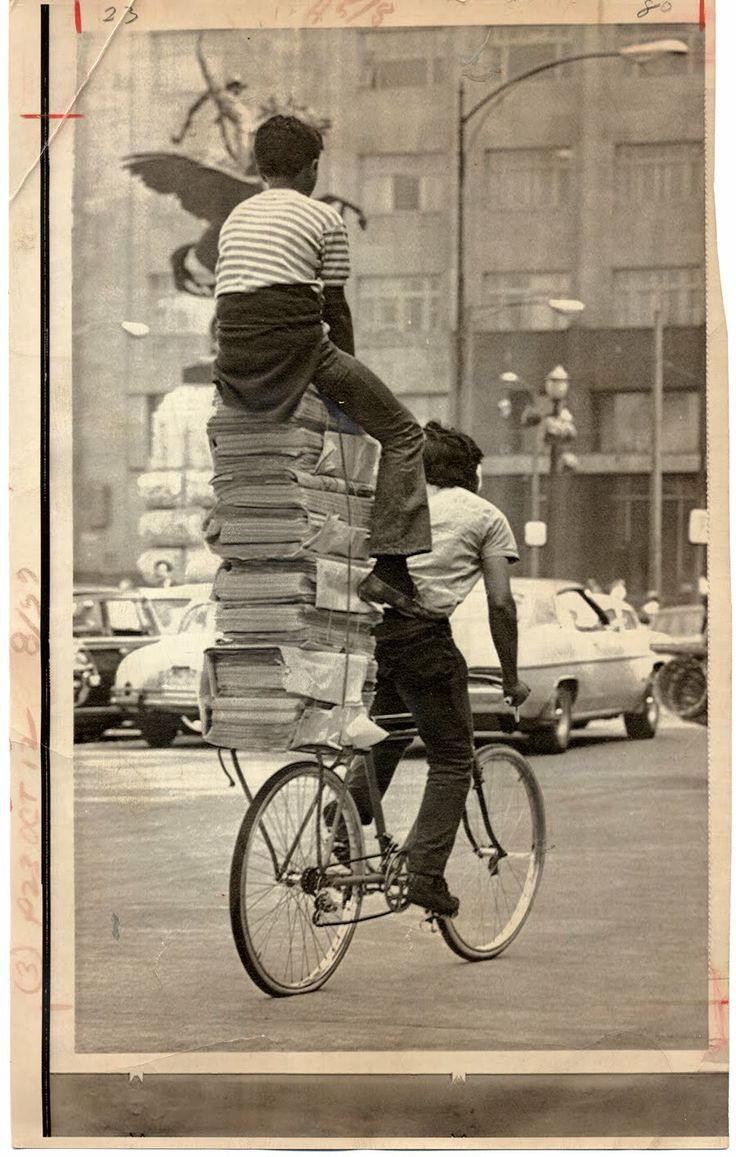 Two boys on a bike - and lots of newspapers!