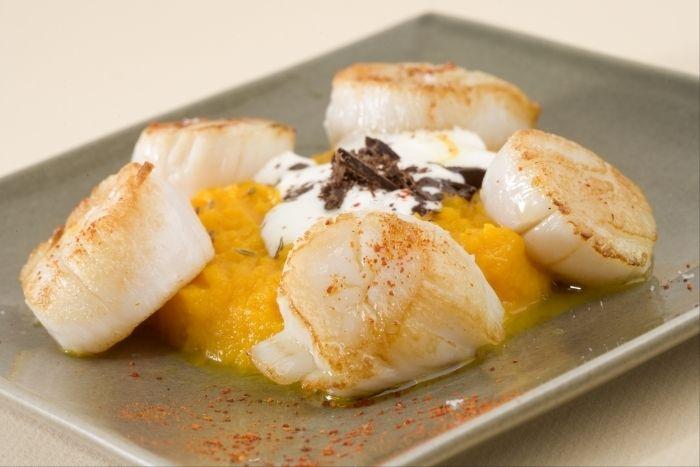 Des noix de Saint Jacques juste saisies, servies avec une crème de carottes cuite avec du cumin et du jus d'orange, et garnie de copeaux de chocolat