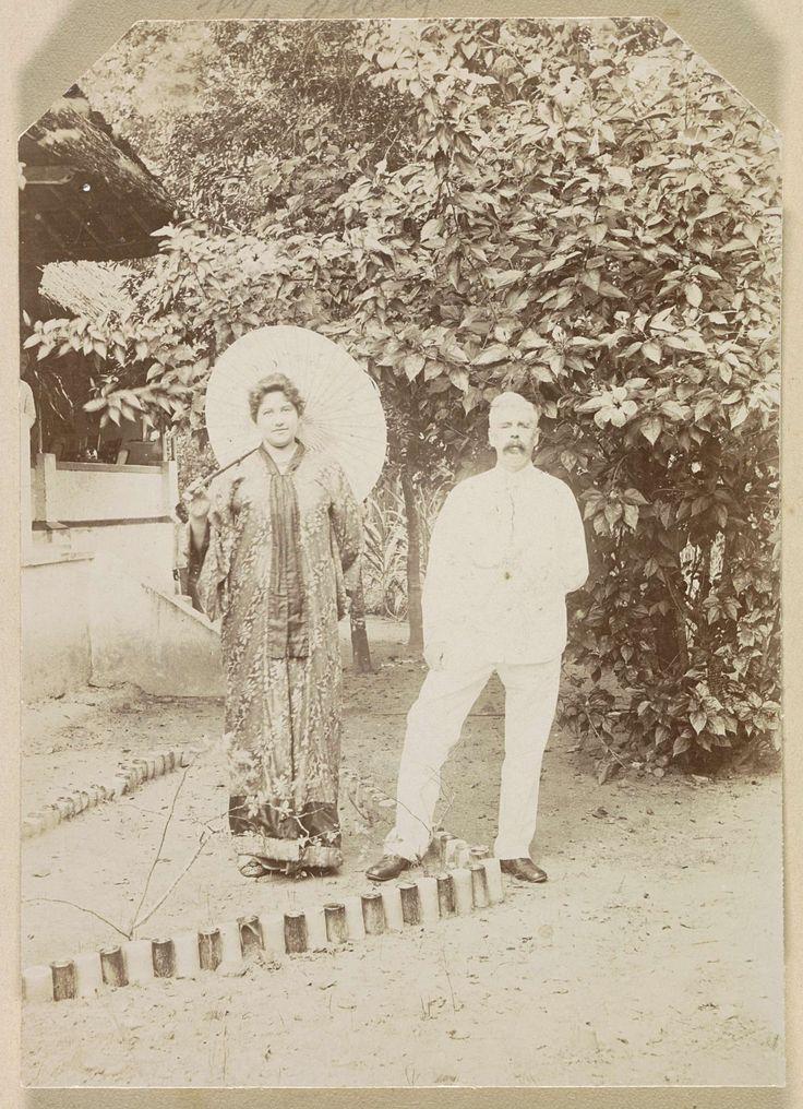 Anonymous | Portret van een Europees echtpaar, vrouw met parasol in Indische dracht, man in licht kostuum, Anonymous, c. 1900 - c. 1920 | Onderdeel van Reisalbum met foto's van Ambon.