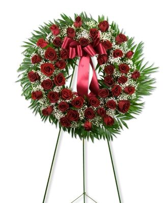 A #wreath of red roses displayed on an #easel. Appropriate for funeral home.
