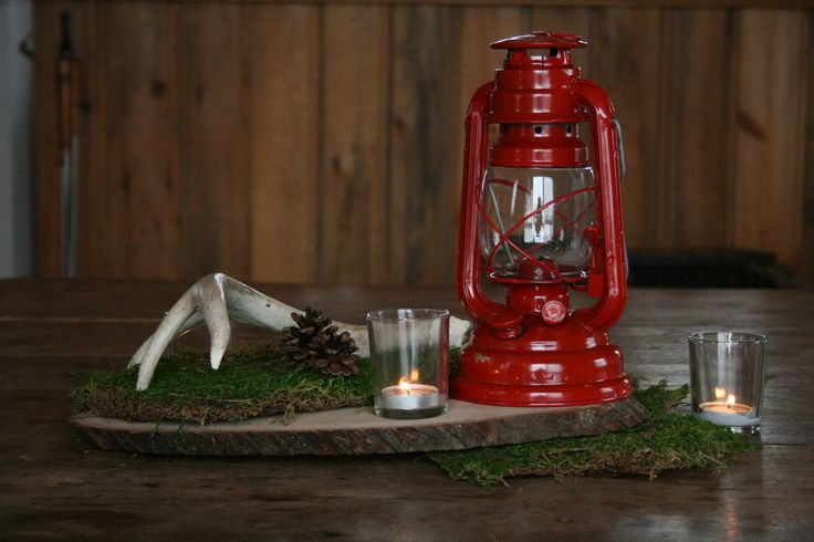 Into the Woods. Cedar base. Deer antler. Red camping lantern. Moss. Pinecones. Candles in votive holders. Is there anyway you can incorporate greenery of some sort into this, or do you have another idea?www.facebook.com/...