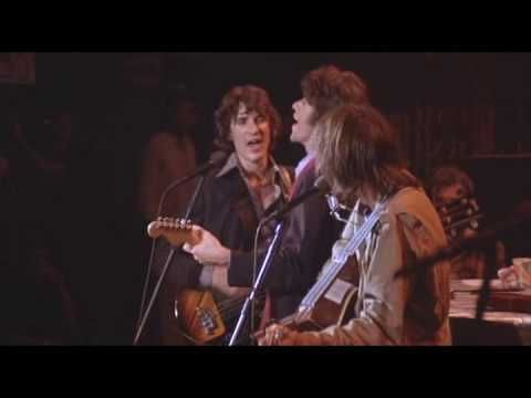Neil Young joins The Band on stage for their final concert. The song, Helpless. Joni Mitchell sings in the shadows.