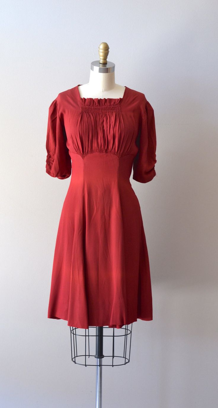 Vintage 1930s deep garnet red rayon crepe dress with slightly squared neckline, puffed elbow length sleeves, gracefully gathered bodice, swingy skirt and two metal zippers at the nape of the neck and side of the waist. ✂-----Measurements    fits like: medium  shoulder: 15  bust: 36-38  waist: 29  hip: 40  length: 39  brand/maker: n/a  condition: there is a faint line of light fade across the skirt, near the hem, see last photo. to ensure a good fit, please read the sizing guide…