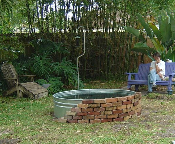 edge with brick (or stone or plants).  OR cut out a large hole in the bottom and place over a newly planted tree to make a raised bed around it.