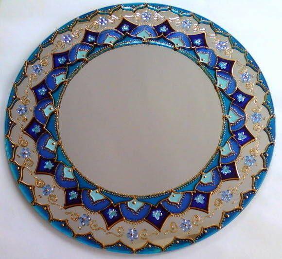Mandala em espelho de 30cm de diâmetro, pintura vitral, decorada com pedrinhas acrílicas e tinta relevo dourada. A parte interna do espelho tem 20cm de diâmetro. Com gancho de metal para ser pendurado na parede.  O espelho é considerado um das nove curas do Feng Shui. Ele pode ser usado para auxiliar na circulação da energia CHI em um ambiente. Pode ser usado para dobrar uma imagem positiva na casa, para aumentar espaços muito estreitos ou pequenos e para iluminar locais muito escuros. São…