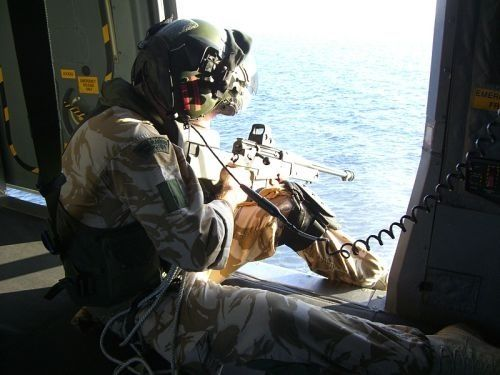 A Royal Marine Commando sits on the deck of a RAF Merlin in anti-pirate operations in Somalia. What is peculiar to note, is the EOTech holographic sight mounted on his AW50.