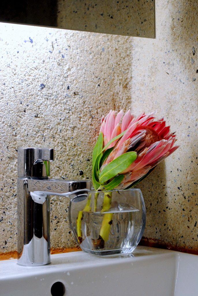 Värikäs protea maljakossa tuo minimalistiseen kylpyhuoneeseen ihanasti naisellisuutta. // Colorful protea brings a feminine atmosphere in this minimalistic bathroom.  Photo by Tuija Talvitie