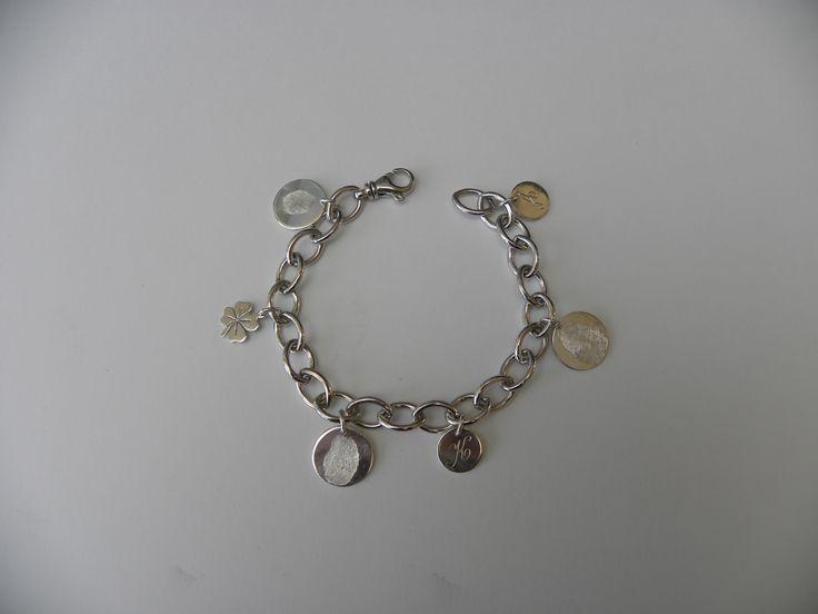 een verrassing voor mama: zilveren armband met 3 vingerafdrukken van de kleinkinderen, 2 eerste letters van de kinderen en een klavertje 4.
