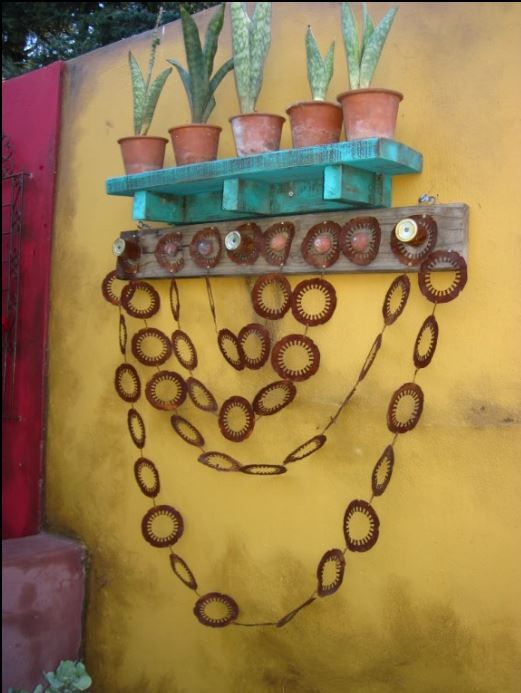 Teal painted wooden shelf, with aged terracotta pots and recycled  material wall art