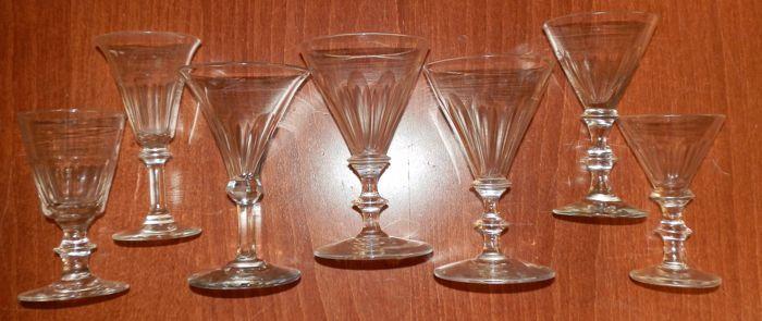 Zeven diverse geslepen knoopglazen 19e eeuw  Zeven transparante antieke mondgeblazen glazen van het model dubbel knoopglas en knoopglas. Ronde voet 4 stuks steel hebben in het midden en aan de bovenzijde een platte knoop. Vijf kelken zijn recht en conisch 2 kelken hebben een lichte radius. De kelken zijn voorzien van geslepen facetten en 1 glas is afgezien van de voet geheel geslepen. Hoogte varieert tussen 120 cm en 95 cm. Diameter kelk varieert tussen 75 cm en 60 cm. Op de onderkant van de…
