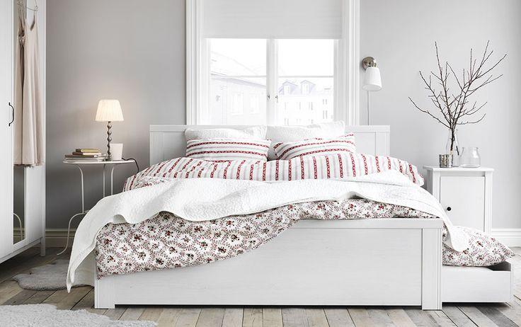 Ein Schlafzimmer mit BRUSALI Bettgestell mit 4 Schubladen in Weiß mit HÅLLROT Bettwäsche-Sets weiß/geblümt, PÄRLHYACINT Bettwäsche-Sets weiß/gestreift und ALINA Tagesdecke und 2 Kissenbezügen in Weiß, LINDVED Beistelltisch in Weiß und BRUSALI Ablagetisch in Weiß
