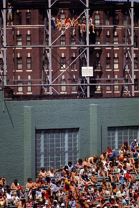 Red Sox fans in the stands and sitting on scaffolding during a 1975 game against the Tigers.  Photographed by: Neil Leifer/SI