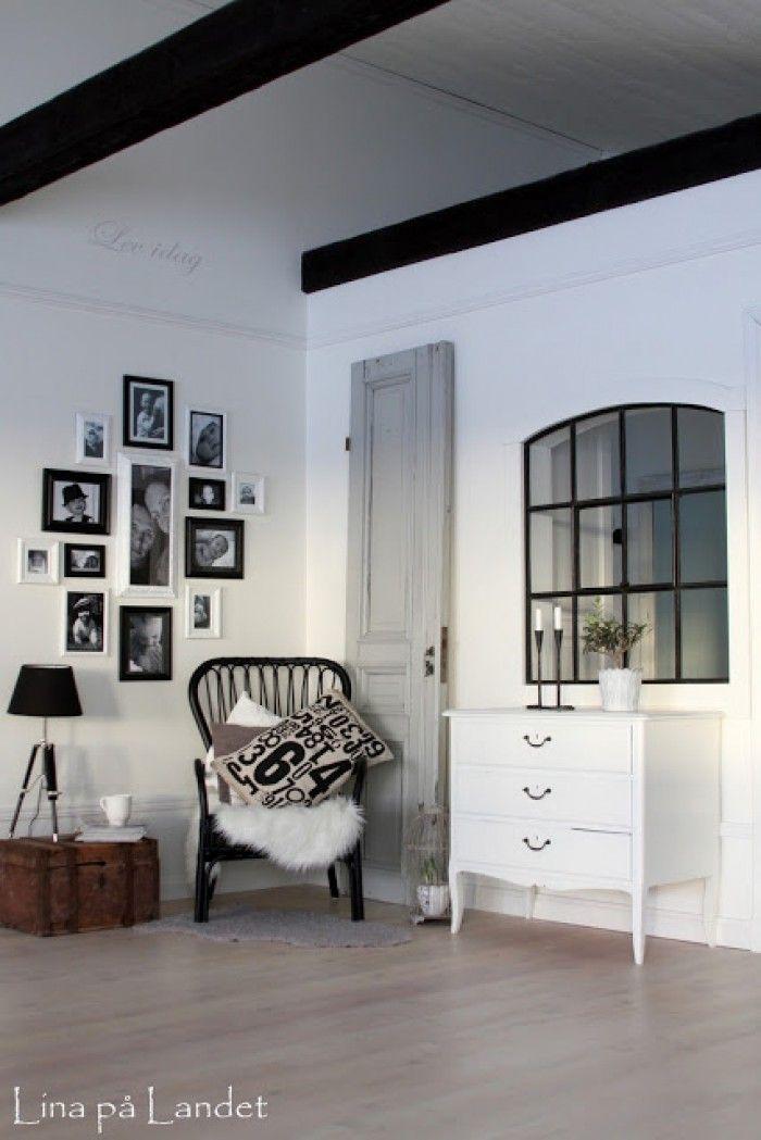 Mooie ruimte in zwart/wit/hout met balkenplafond en binnenraam.