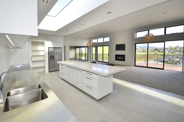Pinfold Place house.  Stainless steel kitchen bench, day pantry and glasses pantry.  David Trubridge light fittings and an Escea fireplace just below the television for those wintery Southern nights!