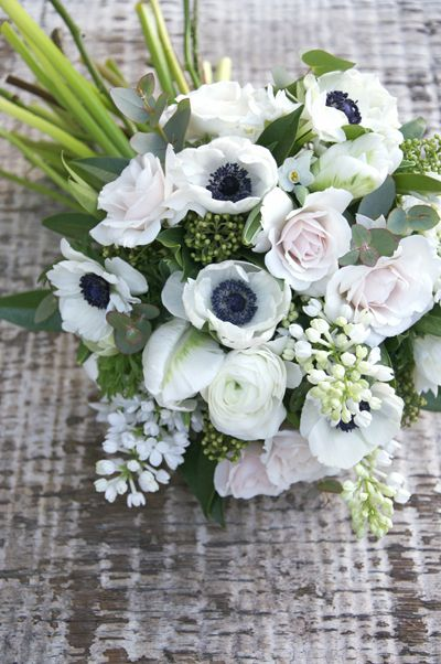 spring inspired wedding bouquet filled with anemones, scented lilac, parrot tulips, skimmia, blush Majolika spray roses and blousy ranunculus