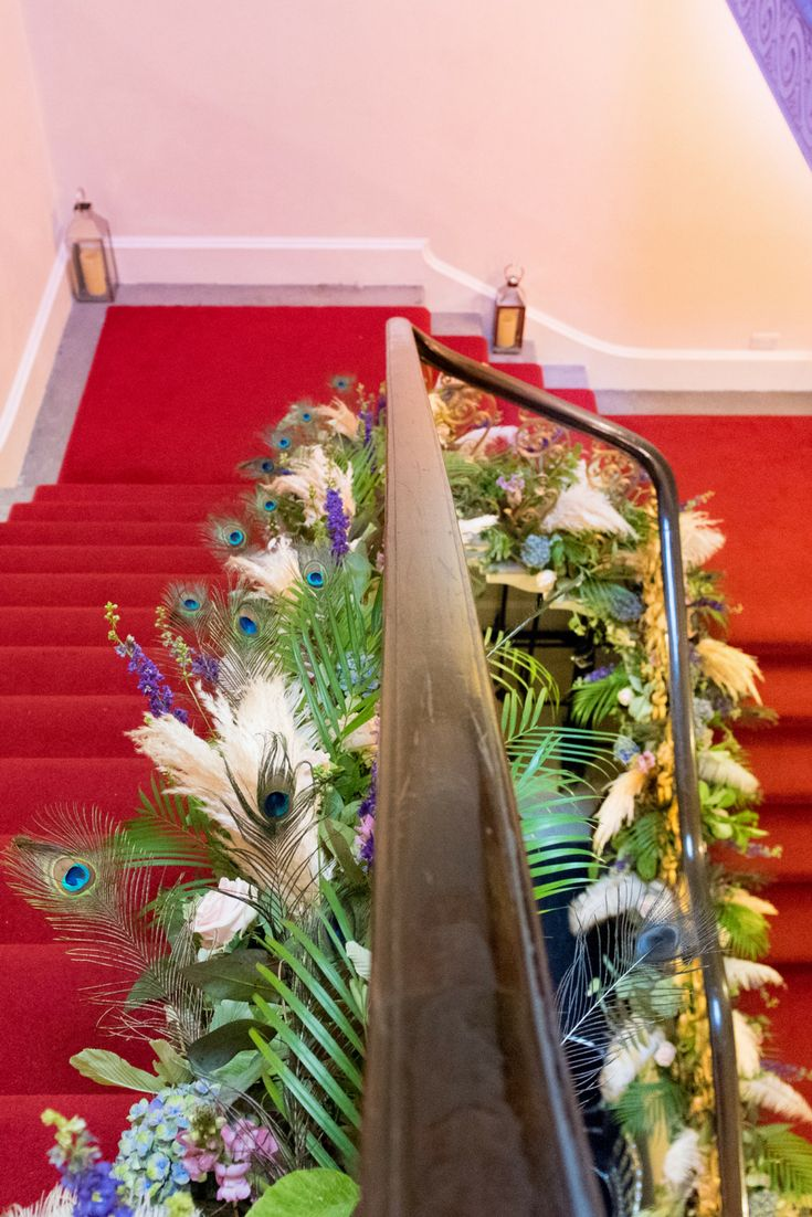 Our dramatic red staircase at Kent House Knightsbridge dressed with cascading flowers and peacock feathers