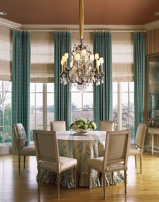 The dining rooms tall windows, dressed in simple drapery panels, offer drama as well as a focused view of the beautiful countryside. Roman shades can be lowered to block the suns rays when needed.