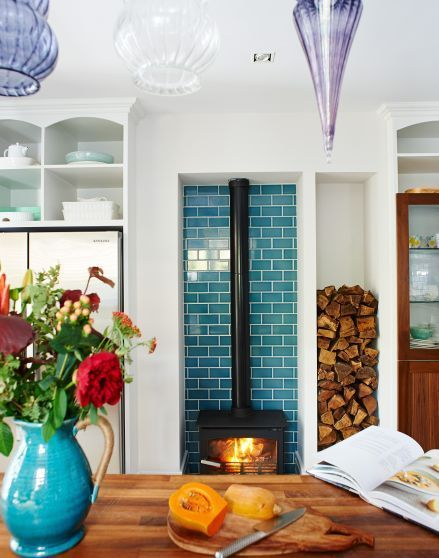 After kitchen design ideas? Take a look at this white modern kitchen with teal tiles and and wood burner for inspiration