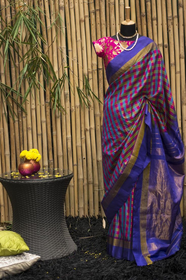 Sensational multicolour checks rule supreme in this chic Gadhwal pure silk saree. A blue gold border with tiny traditional temple motifs and a rich golden blue pallu, make this a truly noteworthy saree. Blue, green, pink or purple…choose your blouse from any color on this saree and light the diva lamp.