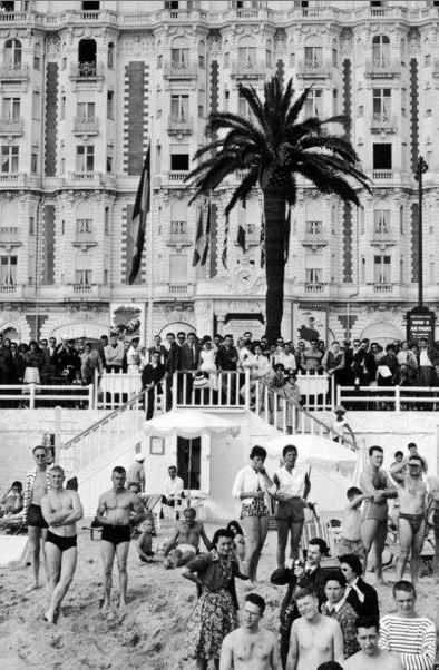 Sunbathers await movie stars in front of the Carlton Hotel in Cannes, 1959