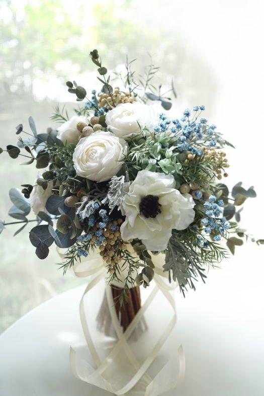 アネモネとブルーの小花をナチュラルに束ねたクラッチブ…