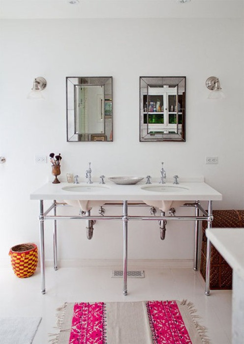 White Bathroom With An Open Double Sink, Simple Lighting And Mirrors BUT  With A Pop Of Color On The Rug.