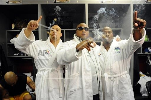 Pittsburgh Steelers linebacker James Farrior (51), nose tackle Casey Hampton (98) and linebacker James Harrison(92) celebrate by smoking cigars and wearing their Super Bowl robes in the locker room after the NFL Super Bowl XLIII football game against the Arizona Cardinals, Sunday Feb. 1, 2009 in Tampa, Fla. The Steelers won 27 to 23.