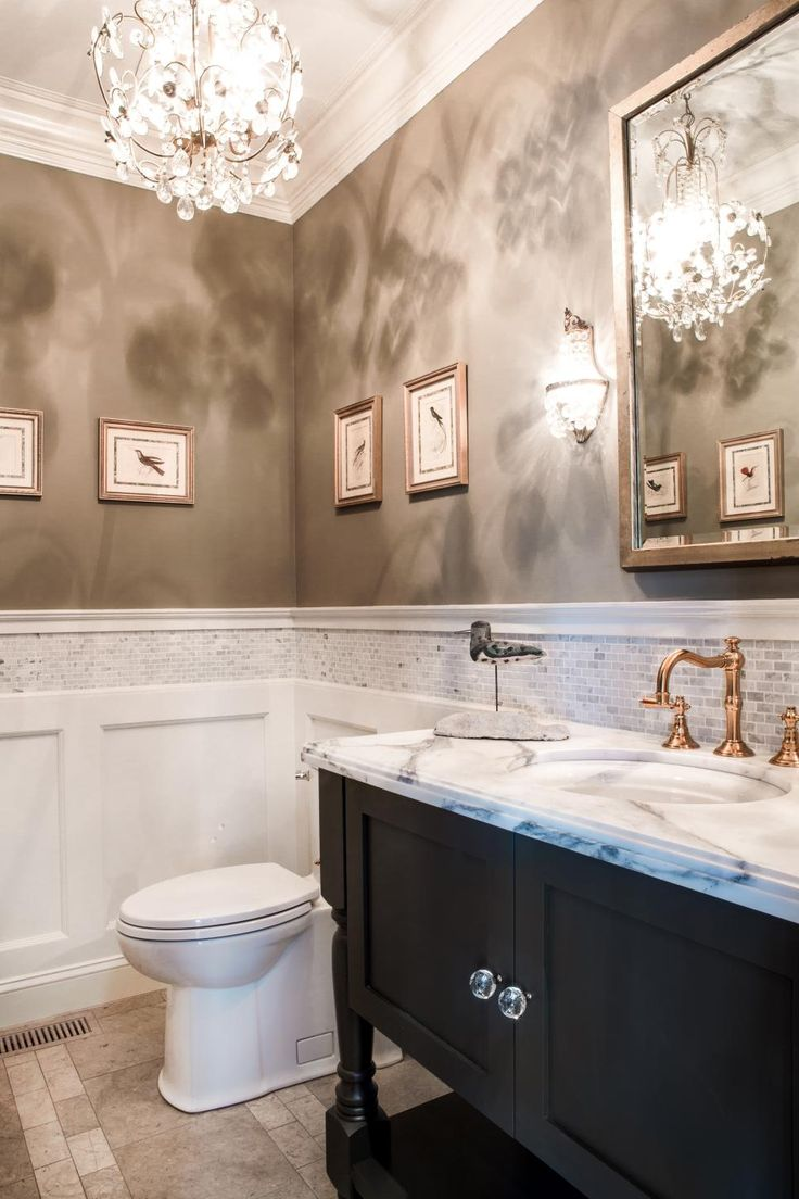 A tile border outlines the split wall in this beautiful traditional bathroom. White paneling provides a break between the neutral floor tile and the neutral wall paint given a marbled look from the elegant hanging chandelier. A copper faucet is echoed with metallic picture and mirror frames. The dark vanity adds a contrast to the bright, warm space.