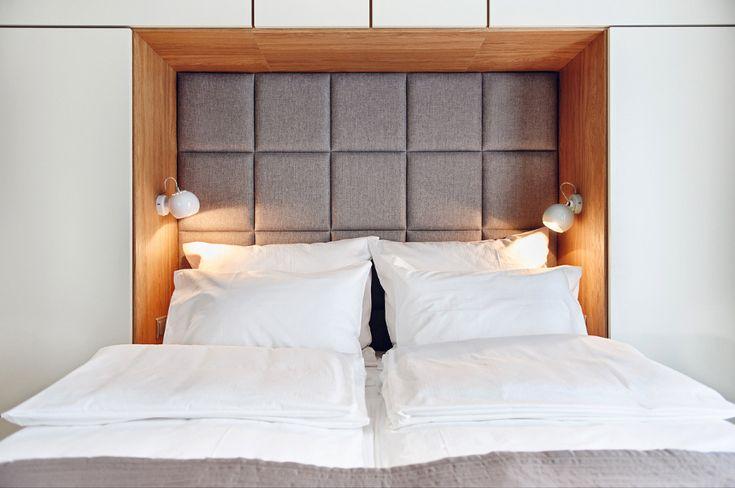 Sypialnia z tapicerowanym wezgłowiem i zabudową nad łóżkiem
