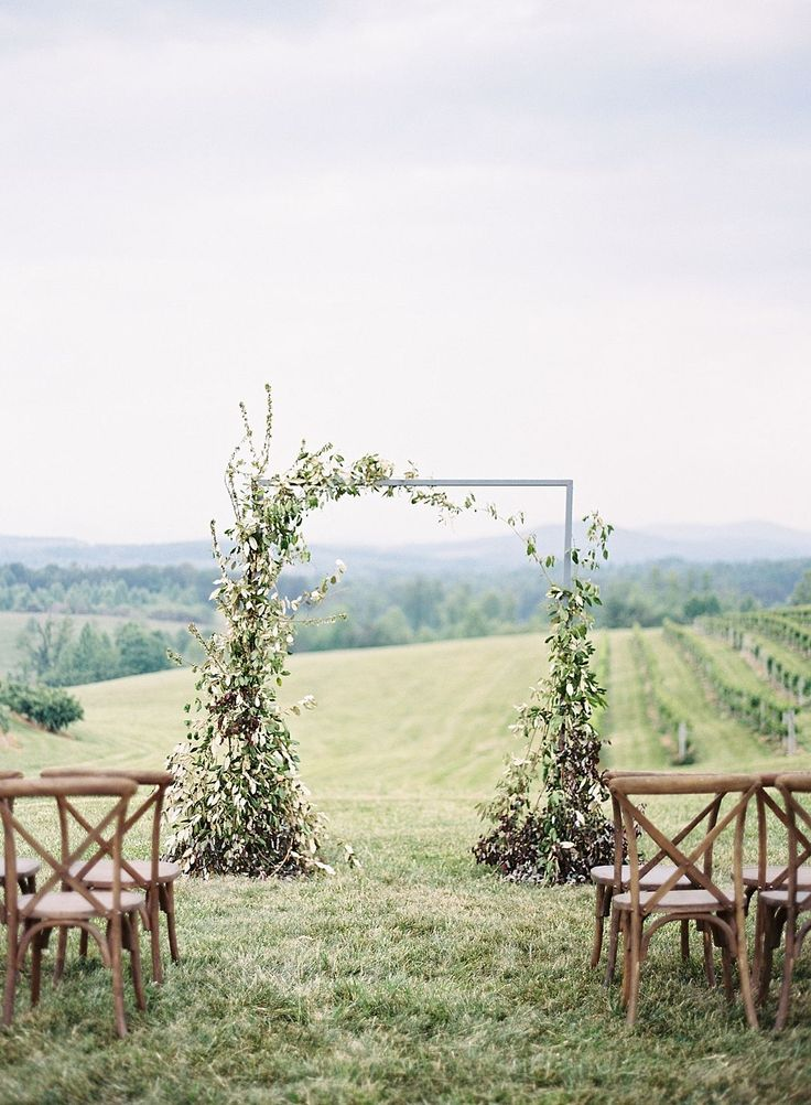 asymmetrical ceremony arch with wild flowers and greens   photo by Chris Isham