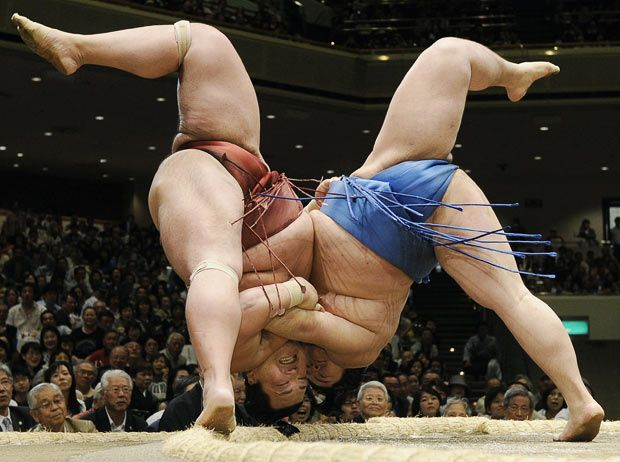 Sumo wrestlers Tosayutaka, right, and Toyohibiki fall to the ground during their bout in the grand summer tournament at Tokyo's Ryogoku Kokugikan sumo arena Photo: AP