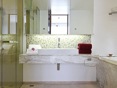 This elegant bathroom with glass shower and vanity really comes alive with its rich, green colour scheme.