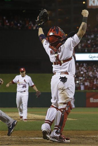 Yadier Molina reacts after Game 6 of the NLCS.. Cards are the 2013 NLCS champs.  10-18-13