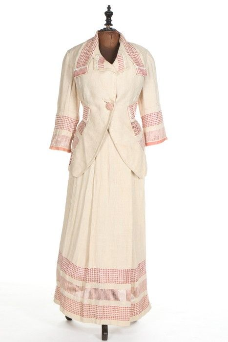 A Pluym lady's summer suit, American, 1912. labelled 'Pluym, Washington DC' and with handwritten client label 'Miss Marguerite Draper, April 1912', of linen open-weave with contrasting pulled and drawn-thread bands in pink silk, with decorative, pink cord, white buttons and pink organdy ruffle trims, bust approx 96cm, 38in, waist 71cm, 28in.