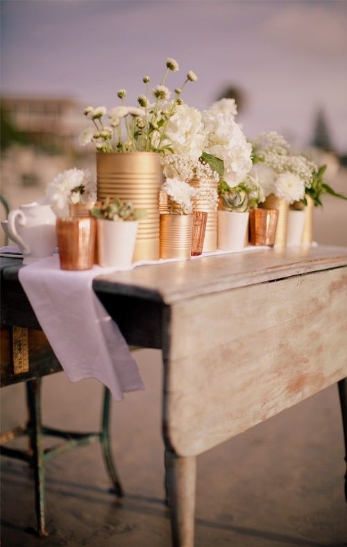 Add some rustic charm to your beach wedding with this DIY tin can project as seen on Shelterness. {DIY tips} An arrangement of these cleaned and empty tin cans that are sprayed using gold and copper spray paint will add muted glamour to your table decor.