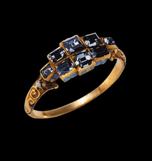 Gold ring, the hoop with leafy scrolls merging with shoulders each engraved with a flower formerly enamelled, supporting a wide bezel set with eight table cut diamonds, the two largest in the centre, flanked by two smaller to each side, and with the smallest two stones on the shoulders. The arcaded sides of the bezel are filled with opaque sky blue enamel. Mid 17th century