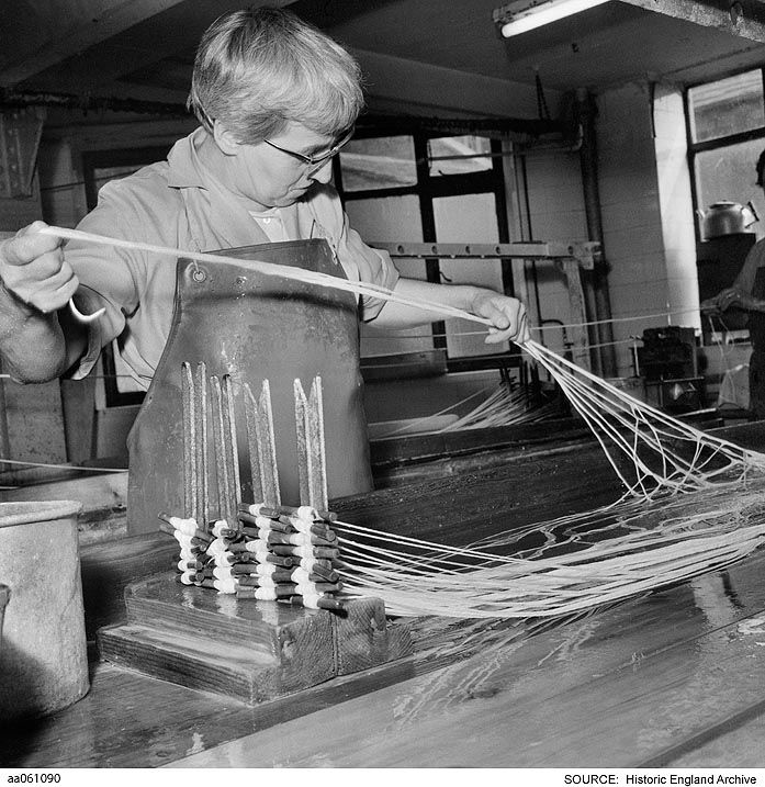 AA061090 Interior view in a factory showing a worker stretching lengths of filament or gut, possibly for use as tennis racquet strings or sausage skins. Location unknown, but likely to be West Yorkshire or East Lancashire  Part of the Eileen Deste 'Nelson and Colne' series of images  Date1960 - 1974 Photographer: Eileen Deste