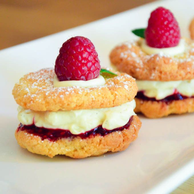 Easy Homemade Monte Carlo Biscuits. Fresh raspberry jam and chantilly cream nestled between crunchy coconut biscuits.