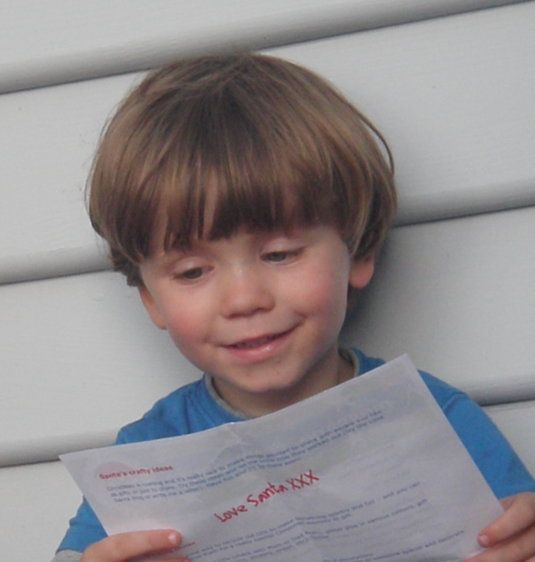 Young boy excited by his Love Santa letter, addressed to him and personalised to his good deeds and gift wants.