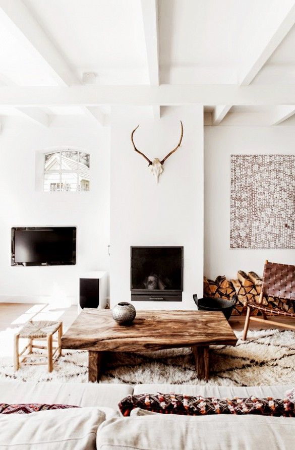 This dutch living room is eclectic and rustic, with a modern twist thanks to it's exposed white beams, leather woven chair, wall antlers and fireplace