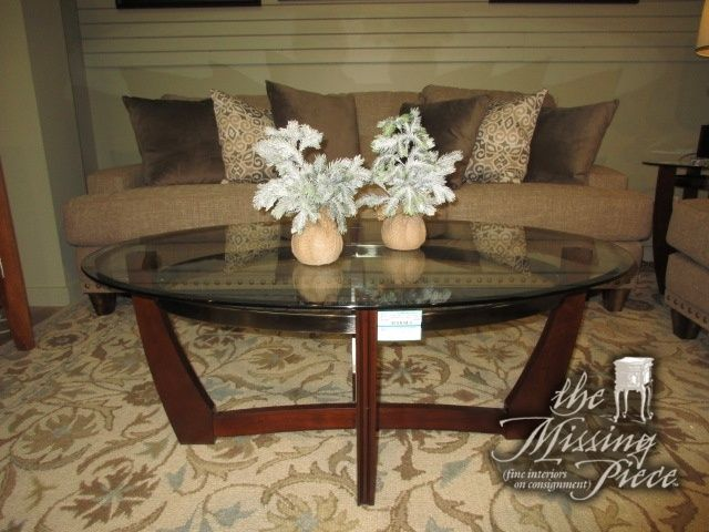 Rooms To Go Oval Glass Top Coffee Table On A Dark Base With Silver Trim.