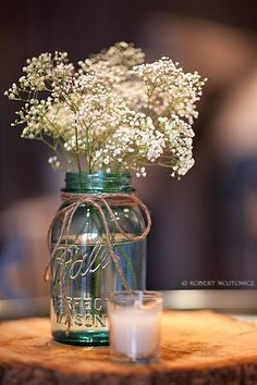 Mason jar, twine, baby's breath, and tree stump as centerpiece