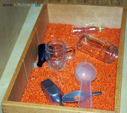Mit Löffeln, Filtern und Glasgefässen können Kinder das Ein- und Umschütten von Linsen üben. Interessant wird es, wenn Gefäße mit unterschie...